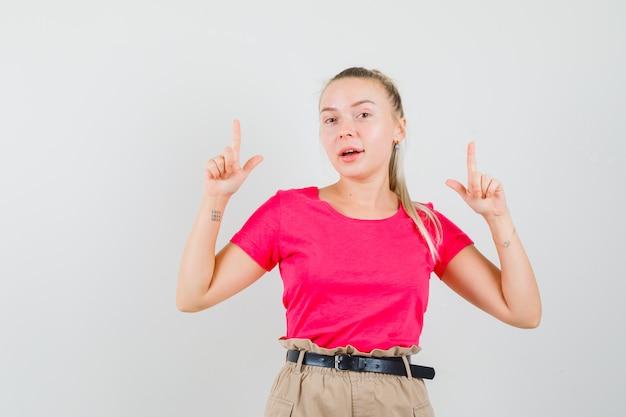 Jonge vrouw die in t-shirt en broek benadrukt en vrolijk kijkt