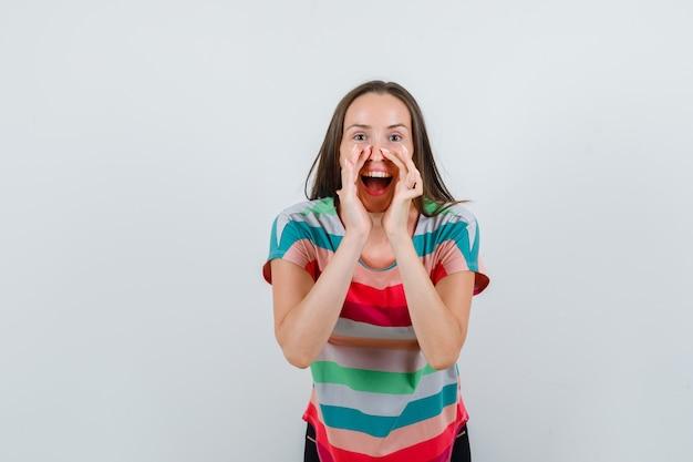 Jonge vrouw die in t-shirt geheim met handen dichtbij mond, vooraanzicht vertelt.