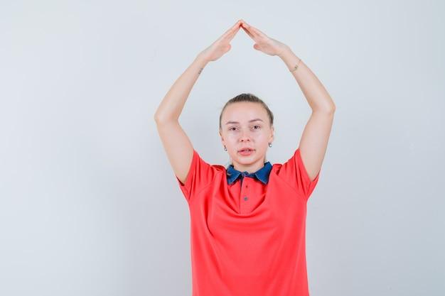 Jonge vrouw die in t-shirt het teken van het huisdak boven het hoofd maakt