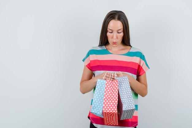 Jonge vrouw die in t-shirt papieren zakken houdt en nieuwsgierig, vooraanzicht kijkt.