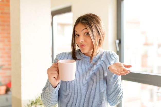 Jonge vrouw die in verwarring en verward met kopje koffie twijfelt