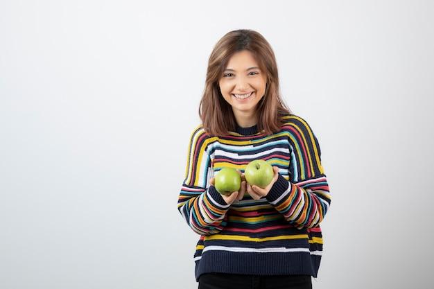 Jonge vrouw die in vrijetijdskleding groene appels met glimlachende uitdrukking houdt.
