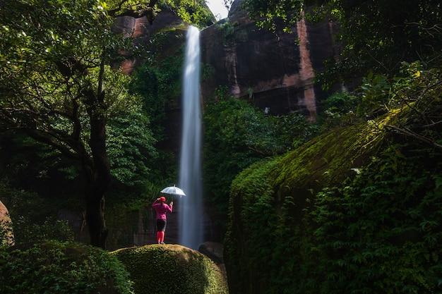 Jonge vrouw die in waterval wandelt