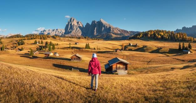 Jonge vrouw die in weiden en bergen zonsondergang in de herfst bekijken