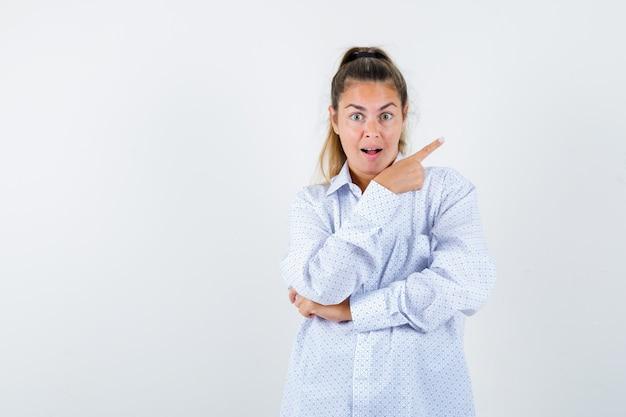 Jonge vrouw die in wit overhemd met wijsvinger naar rechts richt en verbaasd kijkt