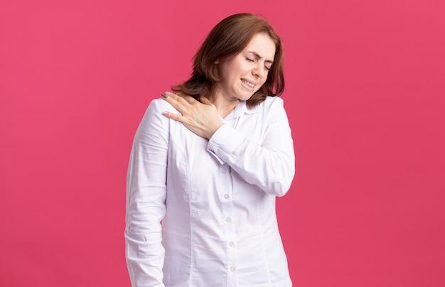 Jonge vrouw die in wit overhemd onwel kijkt wat betreft haar schouder die pijn voelt die zich over roze muur bevindt