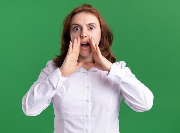 Jonge vrouw die in wit overhemd voorzijde bekijkt die met handen dichtbij mond wordt verrast die zich over groene muur bevindt
