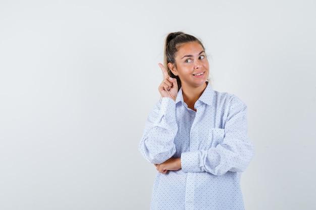 Jonge vrouw die in wit overhemd wijsvinger in eureka-gebaar opheft en verstandig kijkt