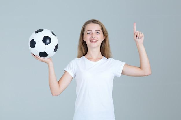 Jonge vrouw die in witte het voetbalbal van de overhemdgreep één vinger benadrukt.