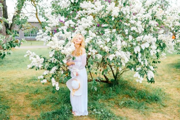 Jonge vrouw die in witte kleding in bloeiend park genieten van