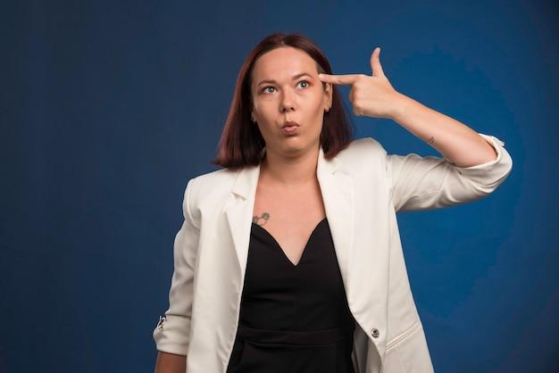 Jonge vrouw die in zwart overhemd kanon tegen haar hoofd zet.