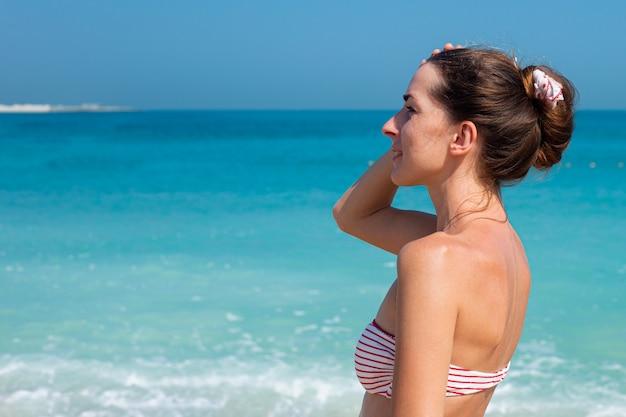 Jonge vrouw die in zwempak haar hoofd houdt dat naar de zee kijkt