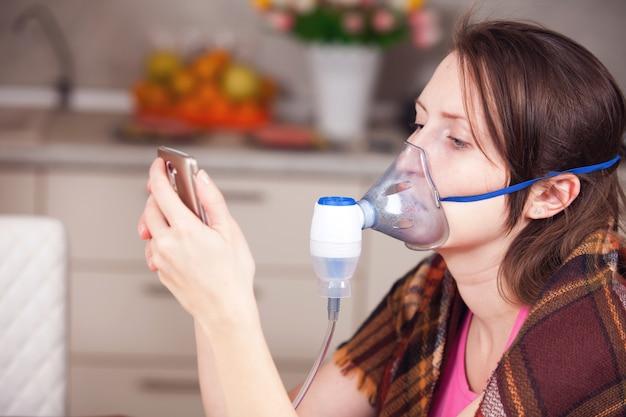 Jonge vrouw die inhalatie met een verstuiver thuis doet