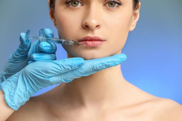 Jonge vrouw die injectie in gezicht krijgt