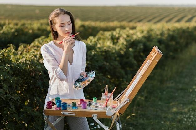 Jonge vrouw die inspiratie in de aard zoekt