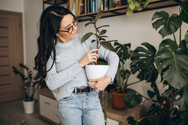 Jonge vrouw die installaties thuis cultiveren