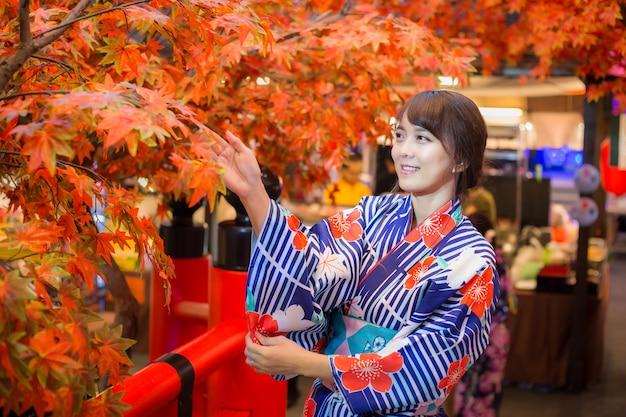 Jonge vrouw die japanse traditionele kimono in de herfstkleur draagt met rode houten brug. japan