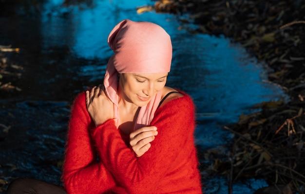 Jonge vrouw die kankerbehandeling ondergaat, zit zichzelf te knuffelen en de zonsondergang in zich op te nemen