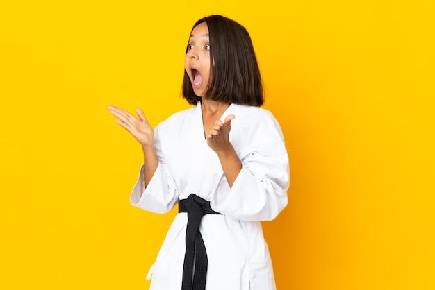 Jonge vrouw die karate doet die op gele achtergrond met verrassingsgelaatsuitdrukking wordt geïsoleerd
