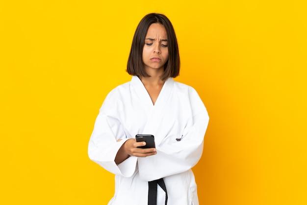 Jonge vrouw die karate doet die op gele achtergrond wordt geïsoleerd die koffie houdt om mee te nemen en een mobiel