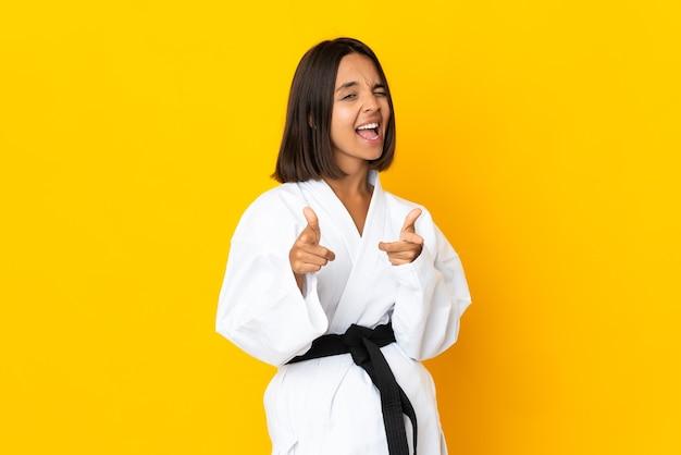 Jonge vrouw die karate doet die op gele achtergrond wordt geïsoleerd die naar voren wijst en glimlacht