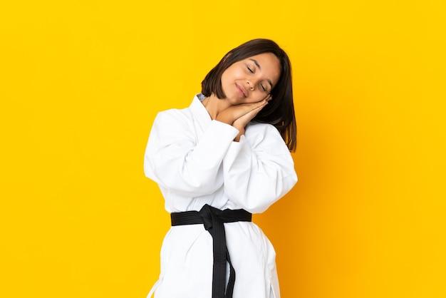 Jonge vrouw die karate doet die op gele achtergrond wordt geïsoleerd die slaapgebaar in mooie uitdrukking maakt