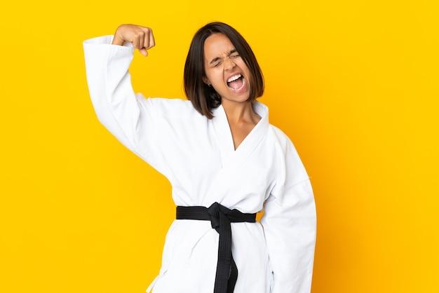 Jonge vrouw die karate doet die op gele achtergrond wordt geïsoleerd die sterk gebaar doet