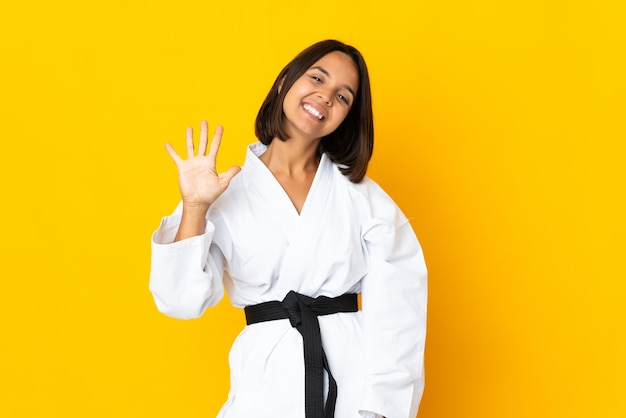 Jonge vrouw die karate doet die op gele achtergrond wordt geïsoleerd die vijf met vingers telt