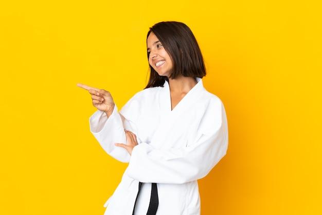 Jonge vrouw die karate doet die op gele achtergrond wordt geïsoleerd die vinger naar de kant richt en een product presenteert