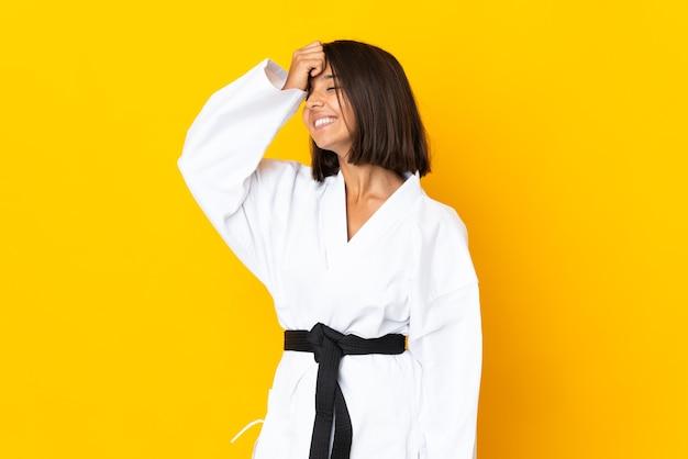 Jonge vrouw die karate doet die op gele achtergrond wordt geïsoleerd, heeft iets gerealiseerd en de oplossing beoogd