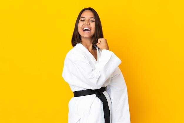 Jonge vrouw die karate doet die op gele muur wordt geïsoleerd die een overwinning viert