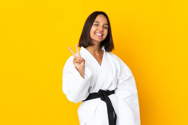 Jonge vrouw die karate doet die op gele muur wordt geïsoleerd die en overwinningsteken glimlacht toont
