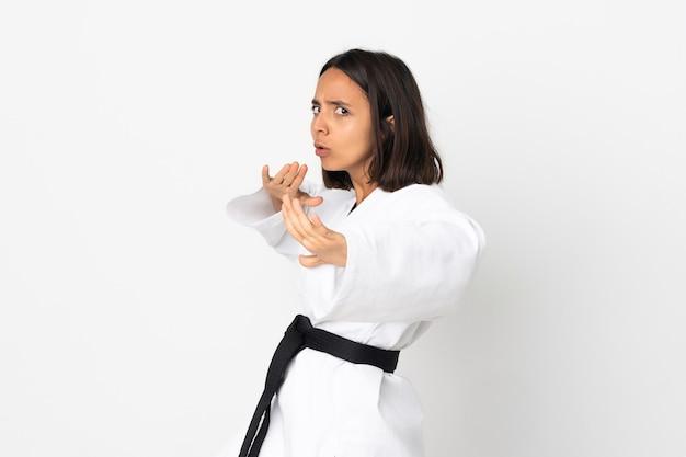 Jonge vrouw die karate doet die op witte achtergrond wordt geïsoleerd