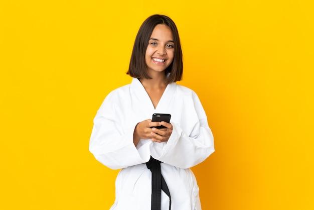Jonge vrouw die karate doet geïsoleerd op een geel oppervlak en een bericht verzendt met de mobiel