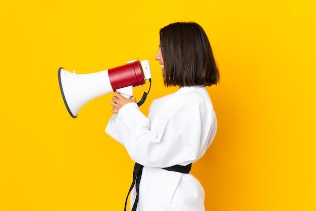 Jonge vrouw die karate doet geïsoleerd op gele achtergrond die door een megafoon schreeuwt