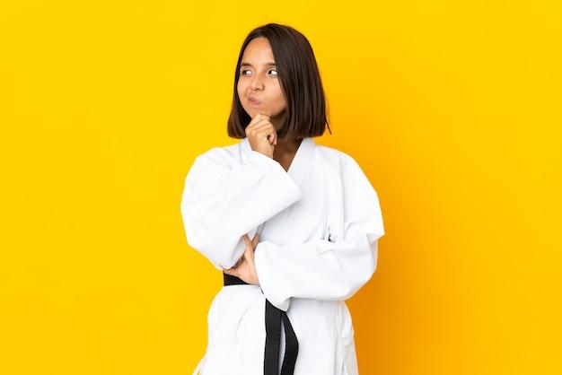 Jonge vrouw die karate doet geïsoleerd op gele achtergrond die twijfels heeft en gezichtsuitdrukking in de war brengt