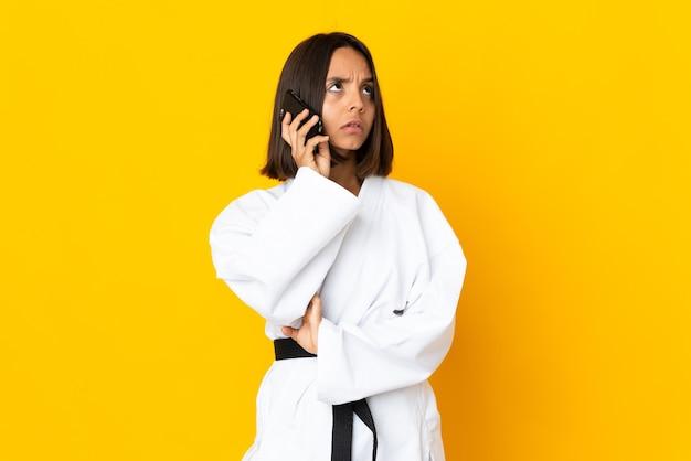 Jonge vrouw die karate doet geïsoleerd op gele achtergrond met koffie om mee te nemen en een mobiel?