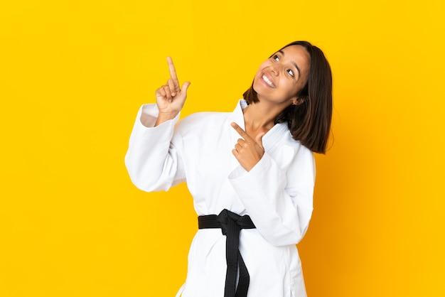 Jonge vrouw die karate doet geïsoleerd op gele achtergrond wijzend met de wijsvinger een geweldig idee