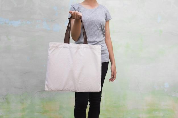 Jonge vrouw die katoenen zak op muurachtergrond houdt. eco concept