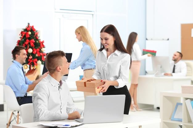 Jonge vrouw die kerstcadeau geeft aan haar collega op kantoor