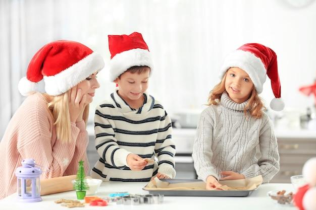 Jonge vrouw die kerstkoekjes bereidt met kleine kinderen in de keuken