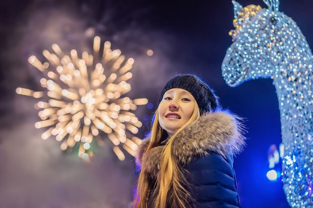 Jonge vrouw die kerstmis viert en kerstmisvuurwerk bekijkt