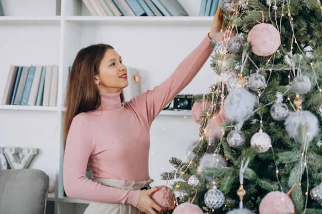 Jonge vrouw die kerstmisboom verfraait