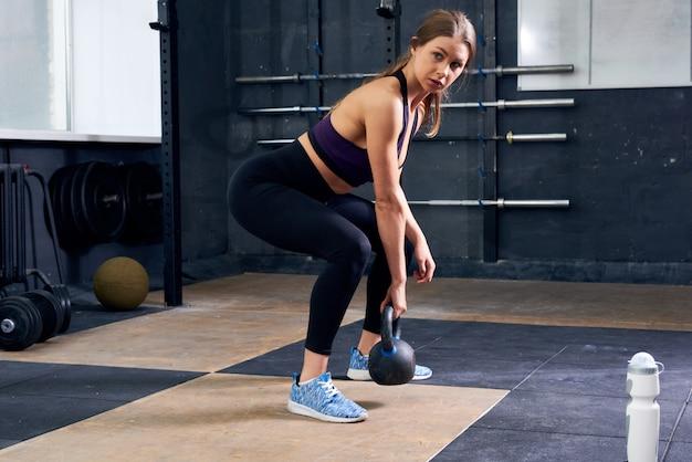 Jonge vrouw die kettlebell in gymnastiek opheft