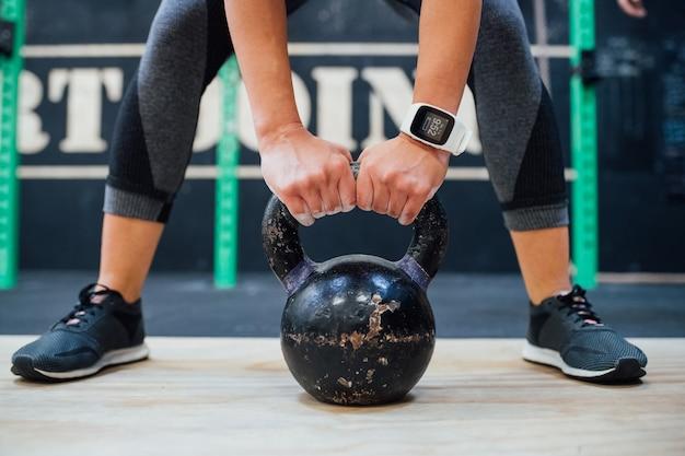 Jonge vrouw die kettlebell indoor gym training