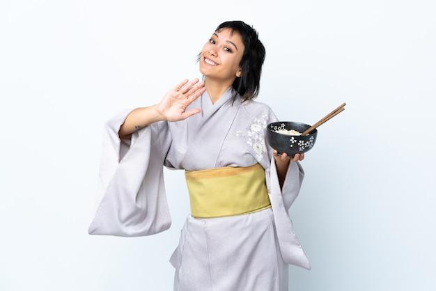 Jonge vrouw die kimono draagt die een kom noedels over het witte muur groeten met hand met gelukkige uitdrukking houdt