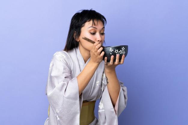Jonge vrouw die kimono over blauwe muur draagt die een kom noedels met eetstokjes houdt en het eet