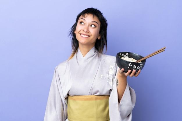 Jonge vrouw die kimono over blauwe muur draagt die omhoog terwijl het glimlachen terwijl het houden van een kom noedels met eetstokjes kijkt
