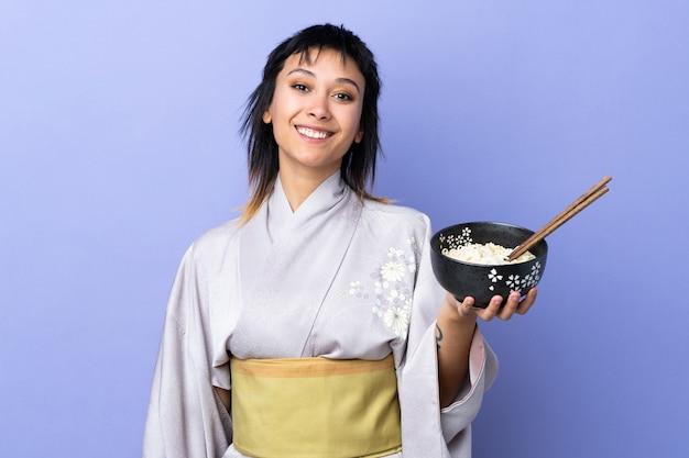 Jonge vrouw die kimono over blauwe muur draagt die veel glimlacht terwijl het houden van een kom noedels met eetstokjes