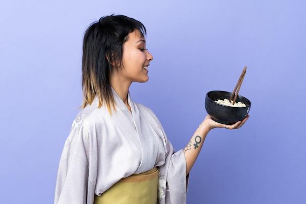Jonge vrouw die kimono over blauwe muur met gelukkige uitdrukking draagt terwijl het houden van een kom noedels met eetstokjes